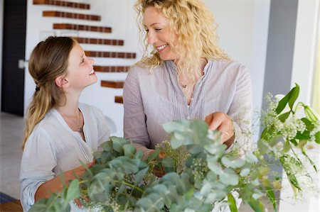 preteen touch - Mid adult woman and her daughter touching leaves and smiling Stock Photo - Premium Royalty-Free, Code: 6108-05870400