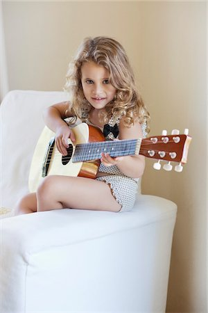 Portrait of a cute little girl playing a guitar Stock Photo - Premium Royalty-Free, Code: 6108-05870434