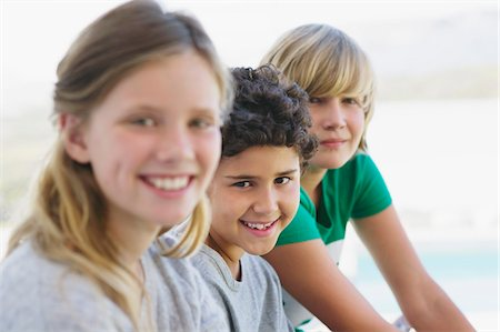 Portrait of a girl smiling with her two brothers Stock Photo - Premium Royalty-Free, Code: 6108-05870581