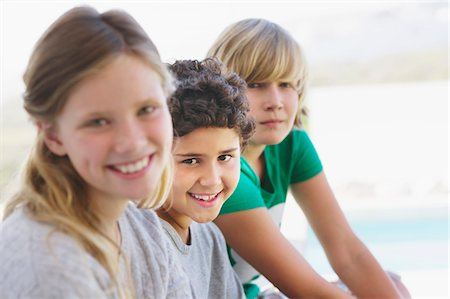 Portrait of a girl smiling with her two brothers Stock Photo - Premium Royalty-Free, Code: 6108-05870600