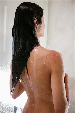 Rear view of woman taking a shower Stock Photo - Premium Royalty-Free, Code: 6108-05870745
