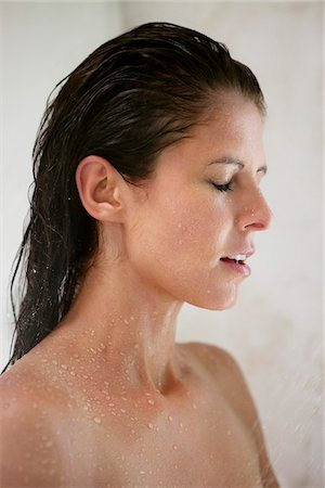 Close-up of a woman taking a shower Stock Photo - Premium Royalty-Free, Code: 6108-05870789