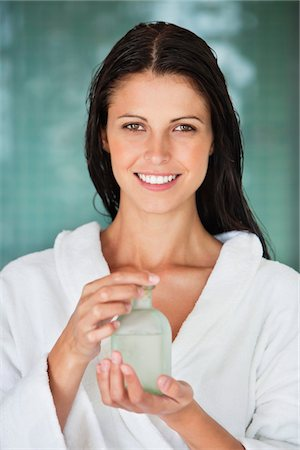 smelly - Portrait of a woman holding a bottle of aromatherapy oil and smiling Stock Photo - Premium Royalty-Free, Code: 6108-05870791