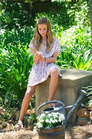 preteen beauty - Cute little girl text messaging while sitting in garden Stock Photo - Premium Royalty-Free, Code: 6108-05871082