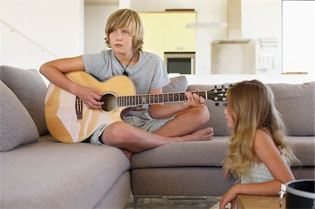 Girl looking at a her brother playing a guitar Stock Photo - Premium Royalty-Free, Code: 6108-05871093
