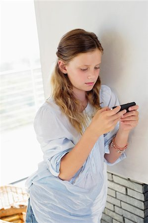 preteen beauty - Girl playing with a handheld video game at home Stock Photo - Premium Royalty-Free, Code: 6108-05871120