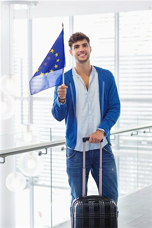 european union - Portrait of a man holding European union flag and a suitcase at an airport Stock Photo - Premium Royalty-Free, Code: 6108-05871285