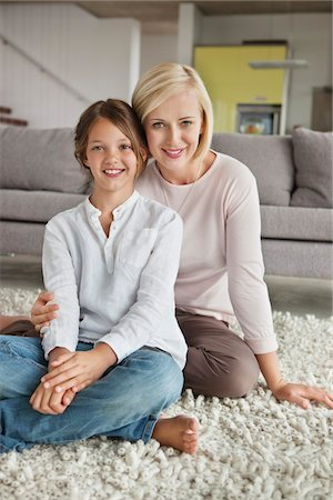 Portrait of a woman with her daughter sitting on carpet Stock Photo - Premium Royalty-Free, Code: 6108-05871233