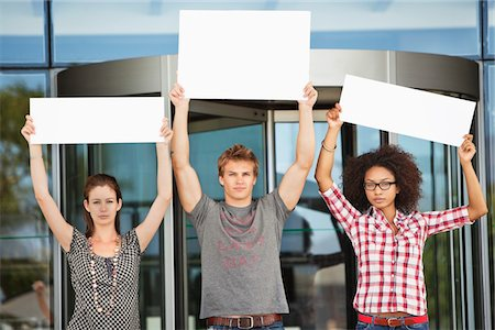 Portrait of three friends protesting with blank placards Stock Photo - Premium Royalty-Free, Code: 6108-05871306