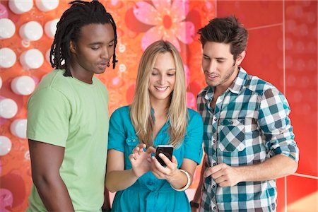 Friends text messaging on a mobile phone in a bar Stock Photo - Premium Royalty-Free, Code: 6108-05871474