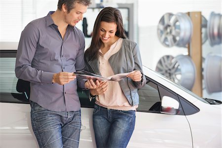 selecting - Couple looking at car catalog in showroom Stock Photo - Premium Royalty-Free, Code: 6108-05871400