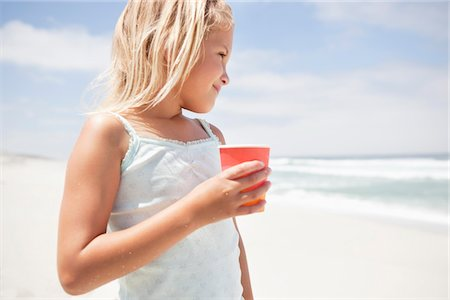 Girl holding a disposable glass on the beach Stock Photo - Premium Royalty-Free, Code: 6108-05871553