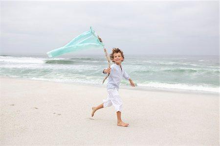 stick - Boy running while holding flag on beach Stock Photo - Premium Royalty-Free, Code: 6108-05871568