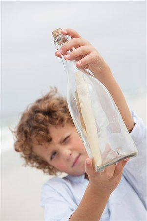 Boy looking at message in a bottle on beach Stock Photo - Premium Royalty-Free, Code: 6108-05871585