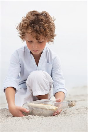 Cute boy looking at message in a bottle on beach Stock Photo - Premium Royalty-Free, Code: 6108-05871589