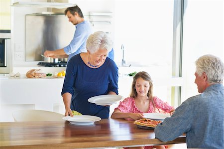 Senior woman placing plates on a dining table Stock Photo - Premium Royalty-Free, Code: 6108-05871528