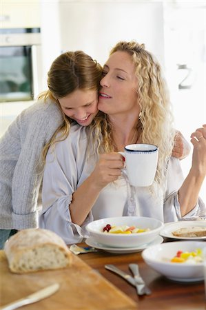 daughter kissing mother - Mid adult woman kissing her daughter at a dining table Stock Photo - Premium Royalty-Free, Code: 6108-05871656