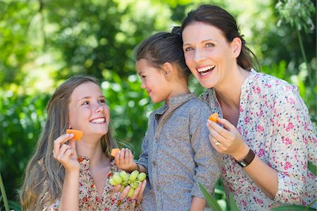 Happy mother eating fruits with her two daughters outdoors Stock Photo - Premium Royalty-Free, Code: 6108-05871930