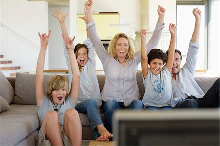 Family watching television set together at home Stock Photo - Premium Royalty-Free, Code: 6108-05872047