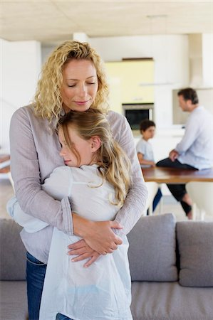 Mother hugging her daughter and smiling Stock Photo - Premium Royalty-Free, Code: 6108-05872066