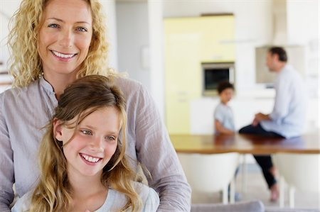 Close-up of a woman and her daughter smiling together Stock Photo - Premium Royalty-Free, Code: 6108-05872037