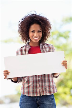 sign - Portrait of a woman holding a blank placard Stock Photo - Premium Royalty-Free, Code: 6108-05872145