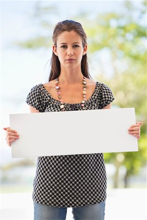 Portrait of a woman holding a blank placard Stock Photo - Premium Royalty-Free, Code: 6108-05872151