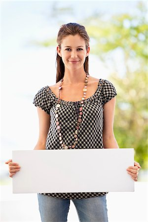 Portrait of a woman holding a blank placard Stock Photo - Premium Royalty-Free, Code: 6108-05872167