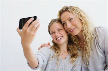 Girl with her mother taking picture of themselves with a mobile phone Stock Photo - Premium Royalty-Free, Code: 6108-05872102