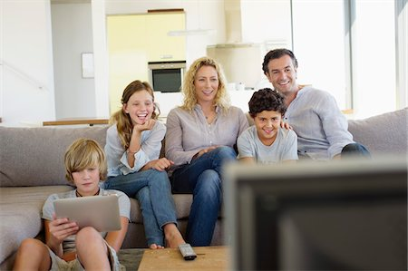 Family watching TV together at home Stock Photo - Premium Royalty-Free, Code: 6108-05872105