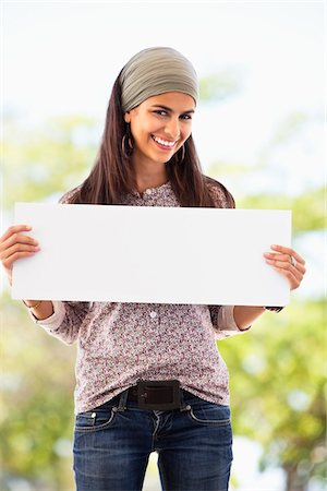 Portrait of a woman holding a blank placard Stock Photo - Premium Royalty-Free, Code: 6108-05872135