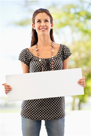 person holding sign - Woman holding a blank placard Stock Photo - Premium Royalty-Free, Code: 6108-05872139