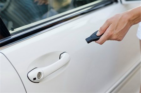 Person's hand unlocking the car with remote control Stock Photo - Premium Royalty-Free, Code: 6108-05872251