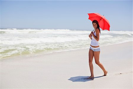 Woman walking on the beach with an umbrella Stock Photo - Premium Royalty-Free, Code: 6108-05872465