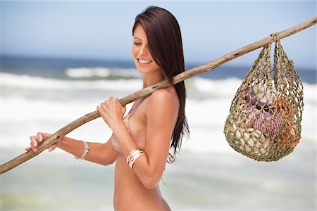 stick - Close-up of a young woman carrying net bag on shoulder Stock Photo - Premium Royalty-Free, Code: 6108-05872482