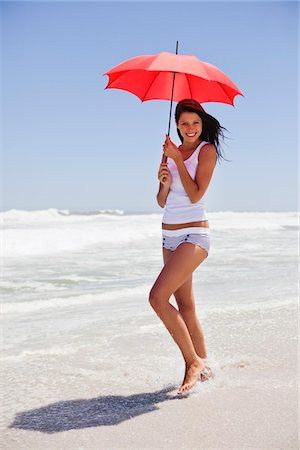 Woman walking on the beach with an umbrella Stock Photo - Premium Royalty-Free, Code: 6108-05872492