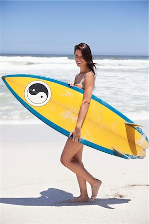 Woman walking on the beach with surfboard Stock Photo - Premium Royalty-Free, Code: 6108-05872432