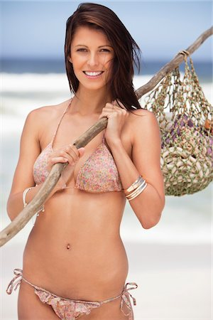 stick - Portrait of a young woman carrying net bag on shoulder Stock Photo - Premium Royalty-Free, Code: 6108-05872500