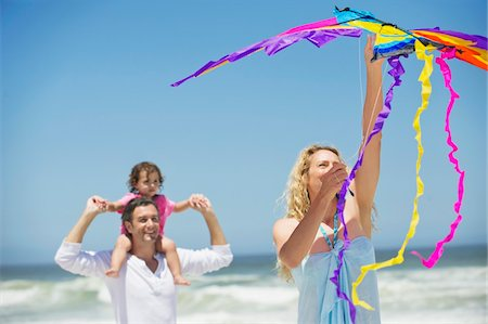 flying happy woman images - Little girl sitting on father's shoulder while mother flying shaped kite on the beach Stock Photo - Premium Royalty-Free, Code: 6108-05872533