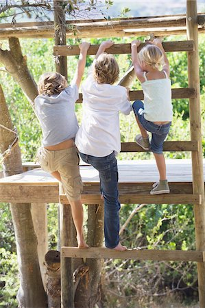 Rear view of children climbing ladders to tree house Stock Photo - Premium Royalty-Free, Code: 6108-05872657