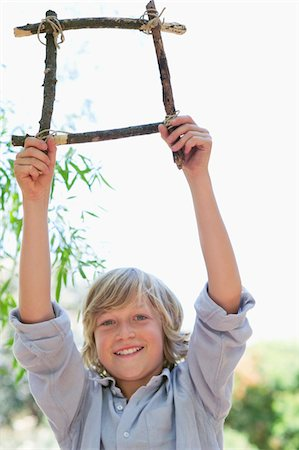 Portrait of a cute little boy holding frame of driftwood with arms raised outdoors Stock Photo - Premium Royalty-Free, Code: 6108-05872663