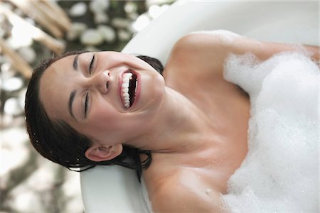 Beautiful young woman taking bubble bath and smiling Stock Photo - Premium Royalty-Free, Code: 6108-05872789