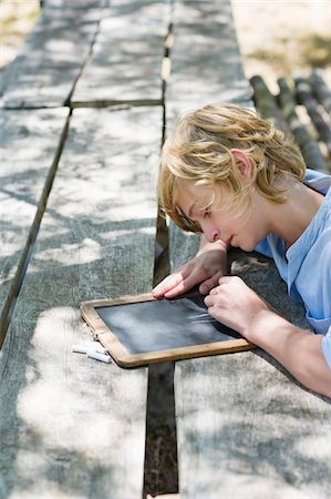 slate - Side profile of a little boy writing on slate outdoors Stock Photo - Premium Royalty-Free, Code: 6108-05872705