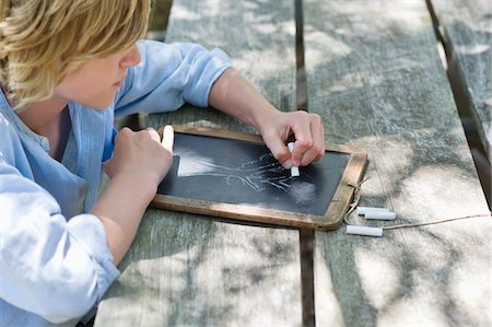 slate - Side profile of a little boy drawing on slate outdoors Stock Photo - Premium Royalty-Free, Code: 6108-05872719