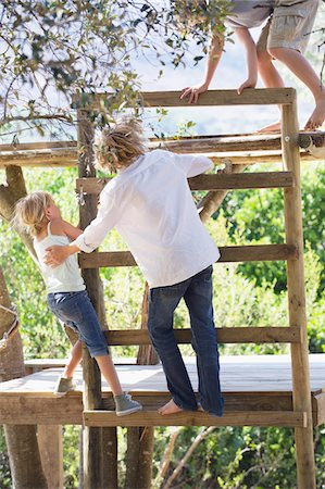 Rear view of children climbing ladders to tree house Stock Photo - Premium Royalty-Free, Code: 6108-05872733