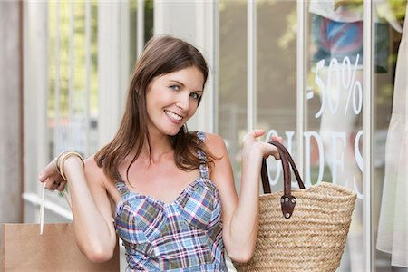 Woman holding shopping bag and smiling, Paris, Ile-de-France, France Stock Photo - Premium Royalty-Free, Code: 6108-05872809