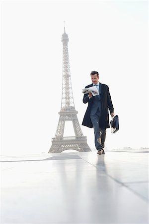 Businessman walking with briefcase reading newspaper with the Eiffel Tower in the background, Paris, Ile-de-France, France Stock Photo - Premium Royalty-Free, Code: 6108-05872902