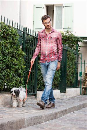 Man holding a dog on leash walking on a sidewalk, Paris, Ile-de-France, France Stock Photo - Premium Royalty-Free, Code: 6108-05873058