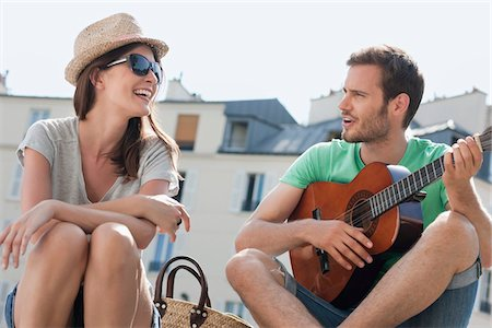 Man playing a guitar with a woman smiling, Canal St Martin, Paris, Ile-de-France, France Stock Photo - Premium Royalty-Free, Code: 6108-05873061