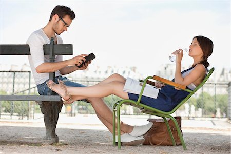 people sitting on bench - Woman drinking water and her husband using a digital tablet, Jardin des Tuileries, Paris, Ile-de-France, France Stock Photo - Premium Royalty-Free, Code: 6108-05873067